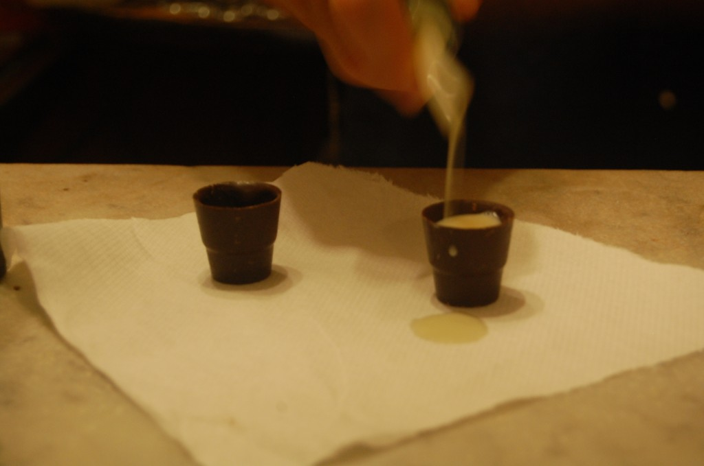 white drink being poured into chocolate shot glasses