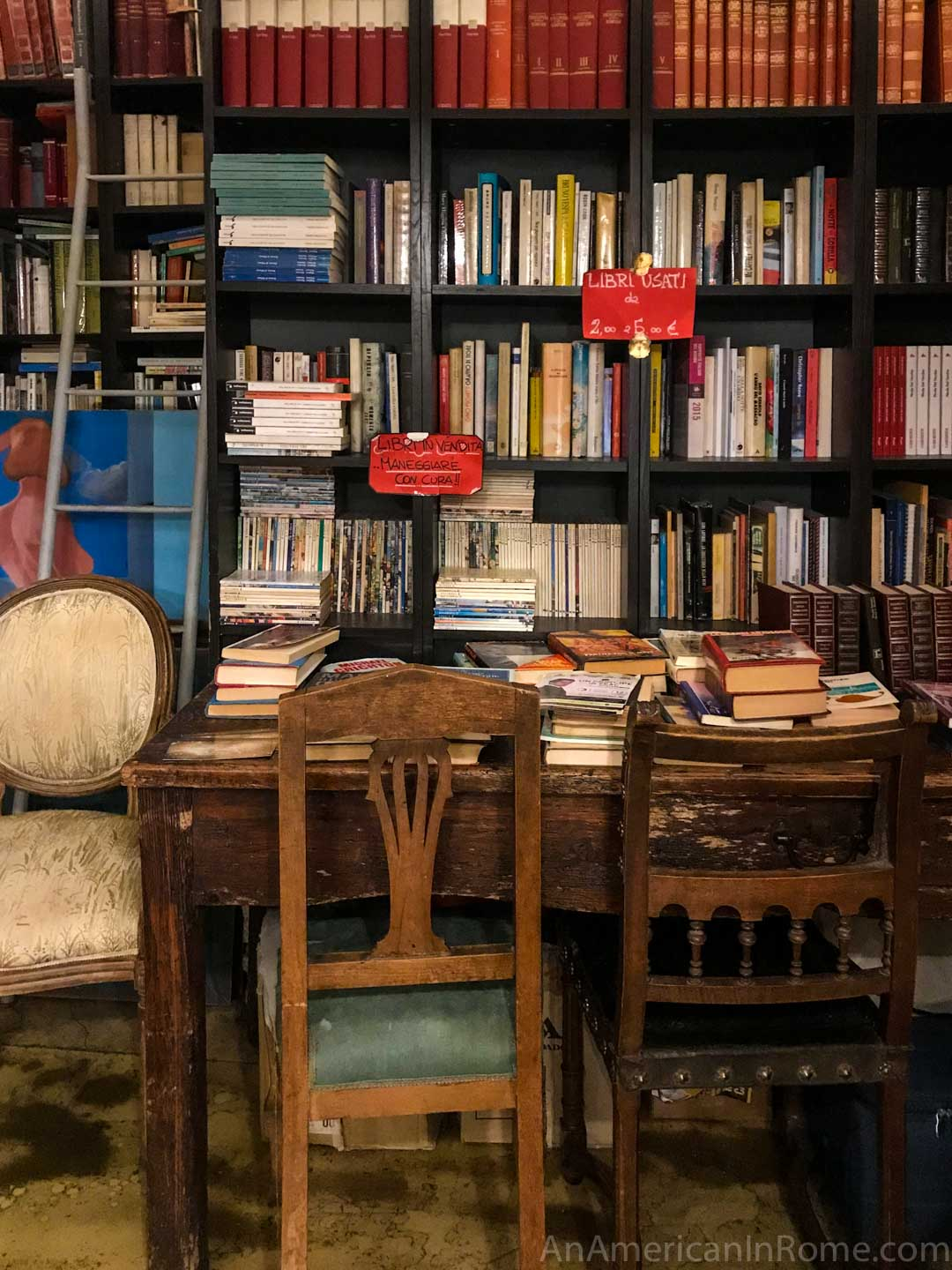 used books on a shelf with antique chairs