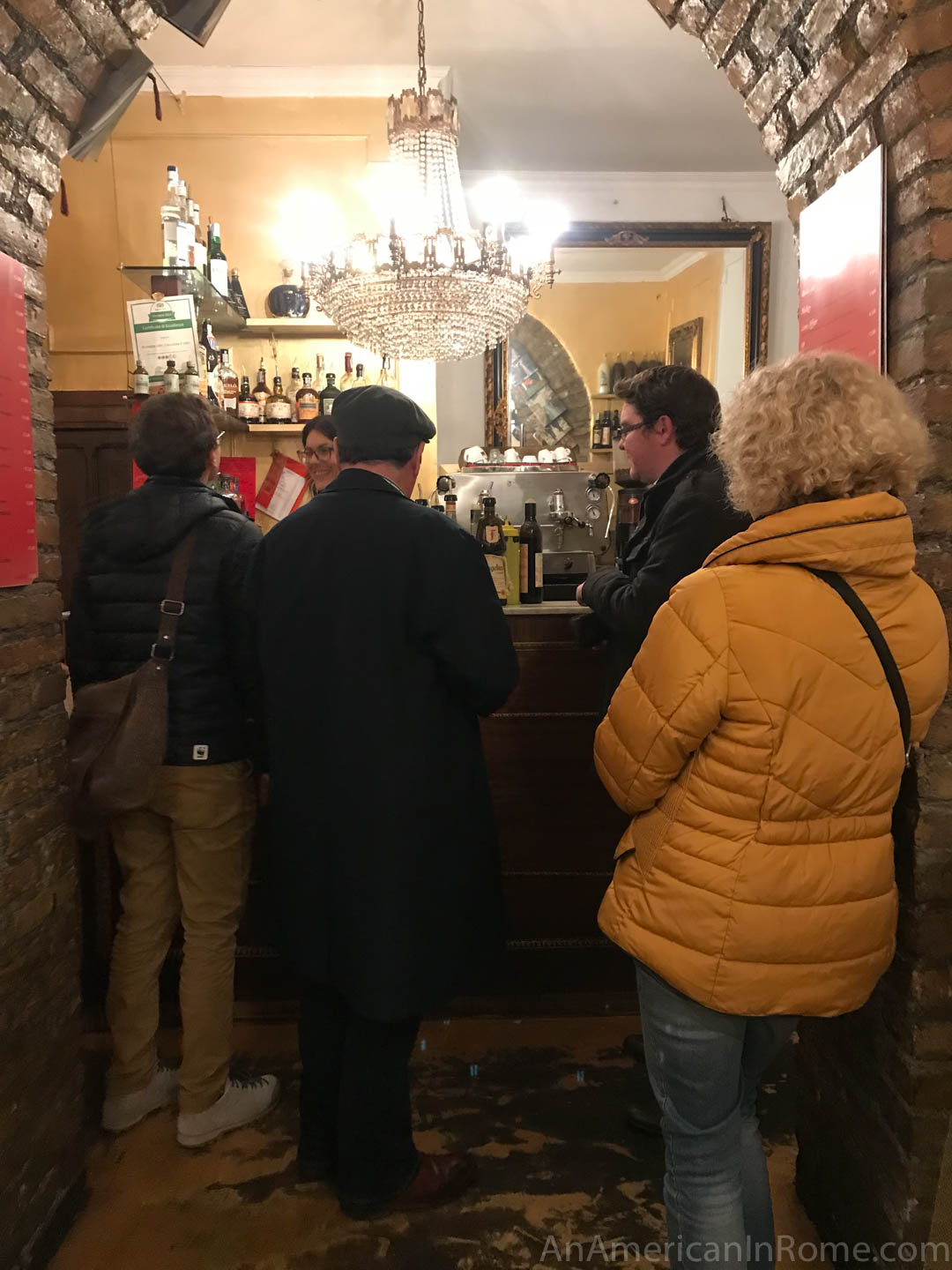 two men and a woman in a yellow coat standing in a small bar