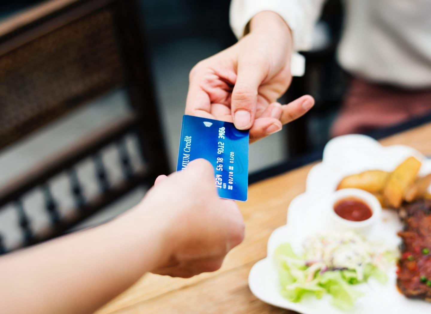 hands touching a blue credit card over food on counter