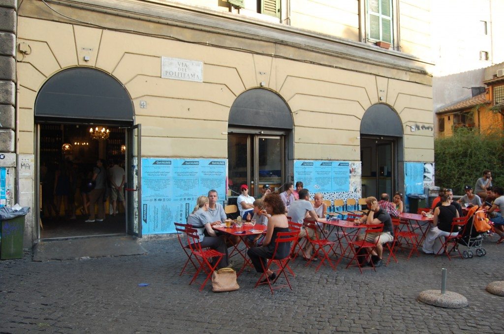Outdoor tables with red chairs in front of Freni e Frizioni in Rome