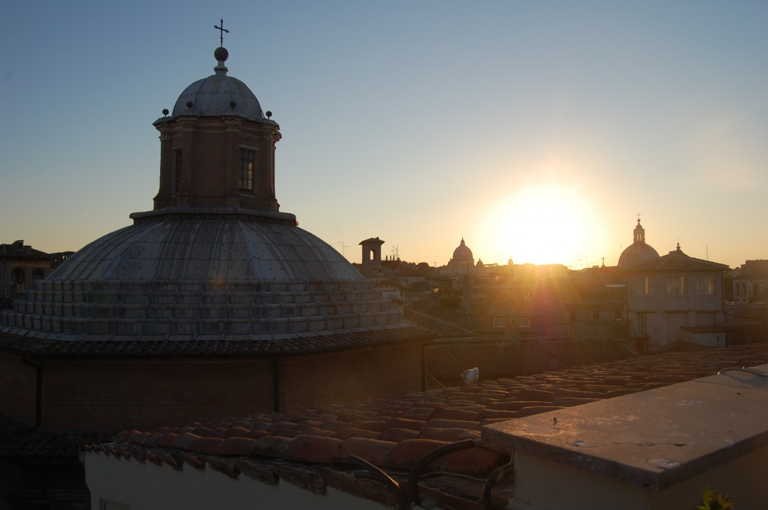 sunset over church domes from the rooftop restaurant at hotel raphael in Rome