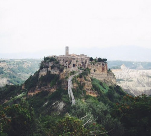 bagnoregio italy stone village on top of a hill with a long bridge leading to it