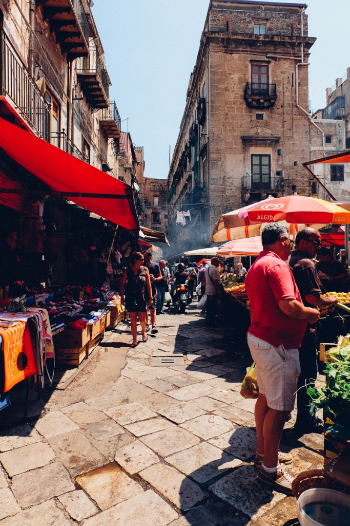 Market in Palermo Sicily with people standing at brightly colored stalls