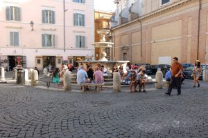 people in the piazza sitting by a fountain in Monti Rome
