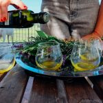 a hand pouring extra virgin olive oil into two tasting glasses on a silver platter