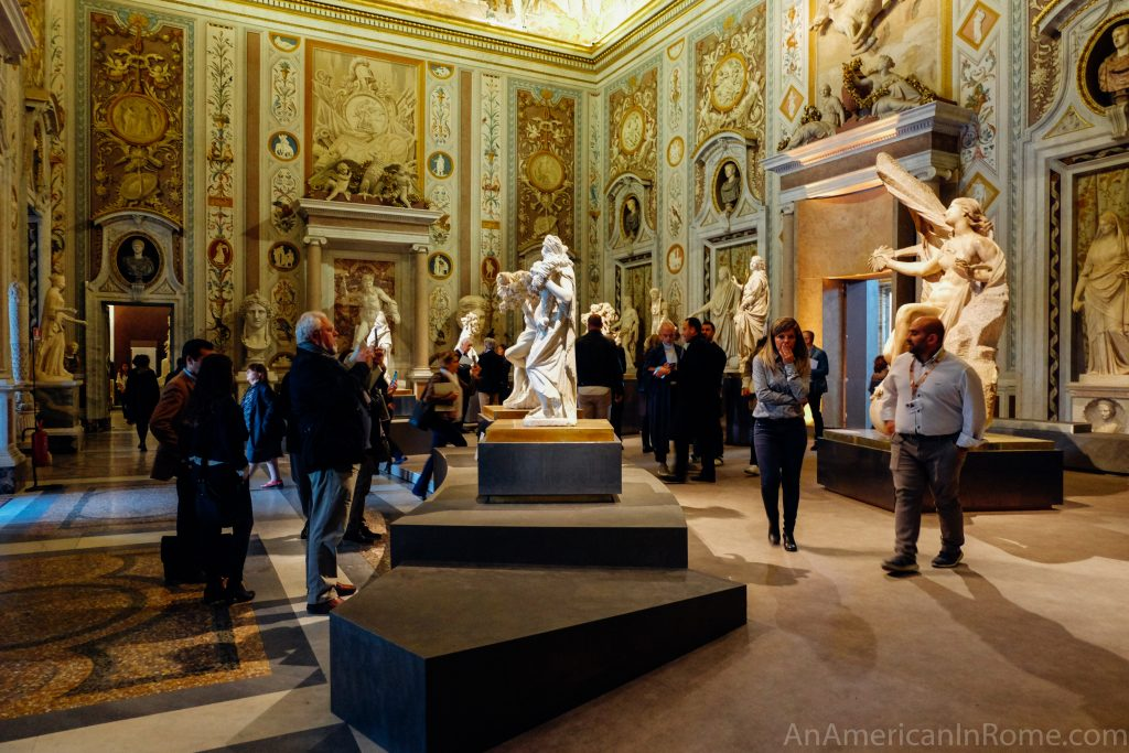 people walking around a statue in galleria borghese