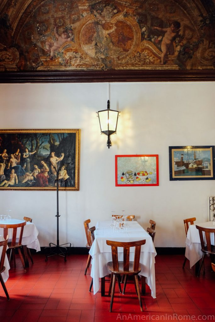 frescoes and tables inside Al Pompiere restaurant in Rome