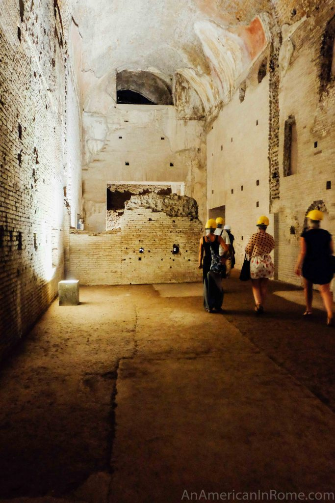 five figures walk away from the camera inside the domus aurea ruins