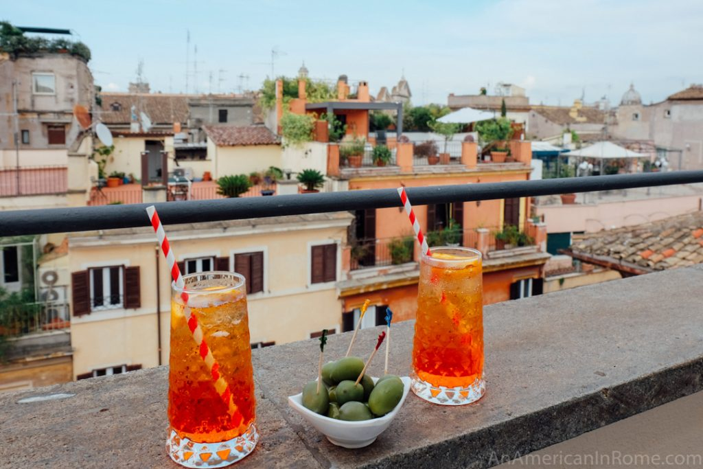 two red spritz cocktails on the edge of a rooftop in Rome with a bowl of green olives