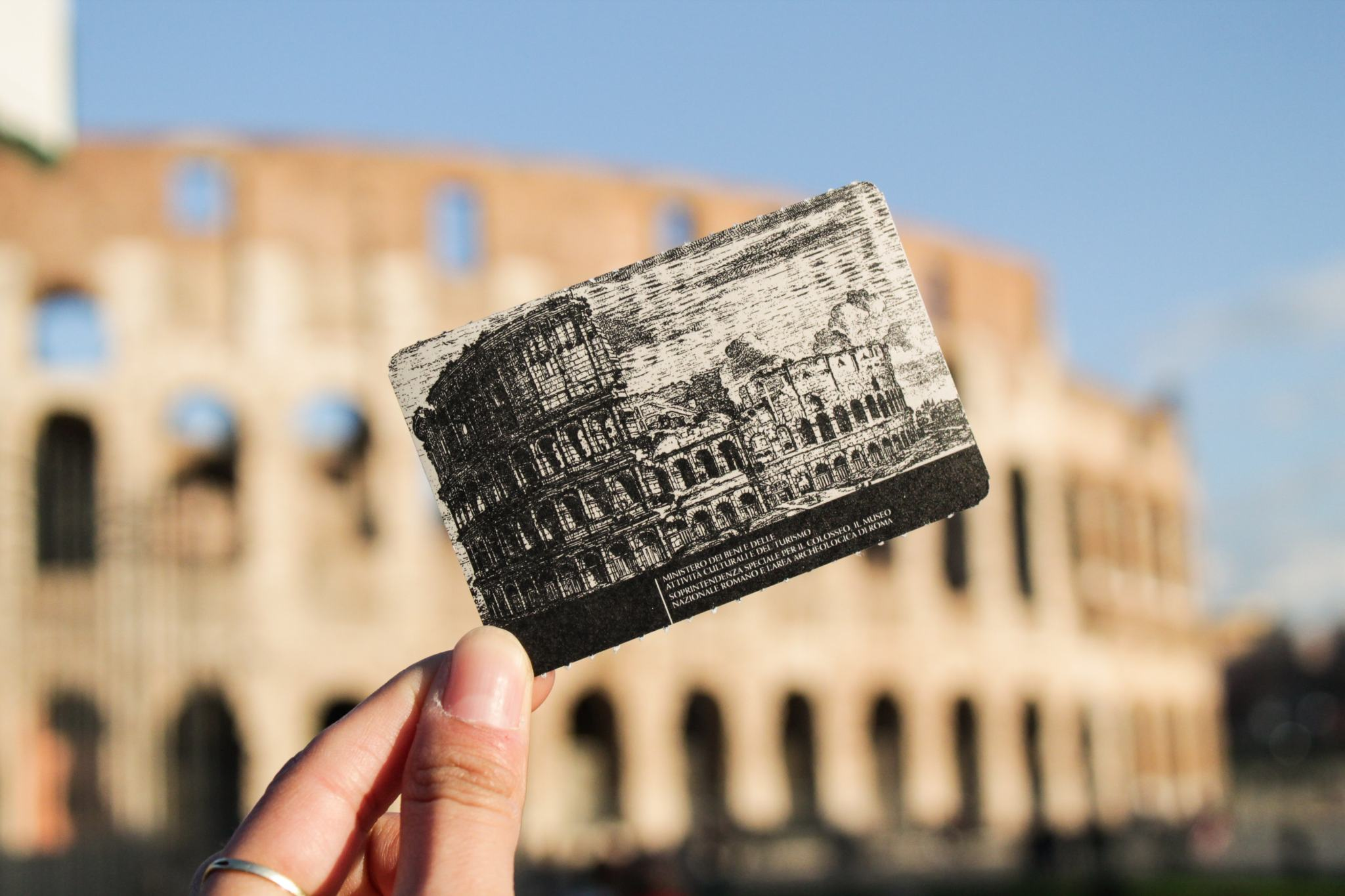 skip the line tickets for the colosseum with hand holding ticket in front of the rome monument