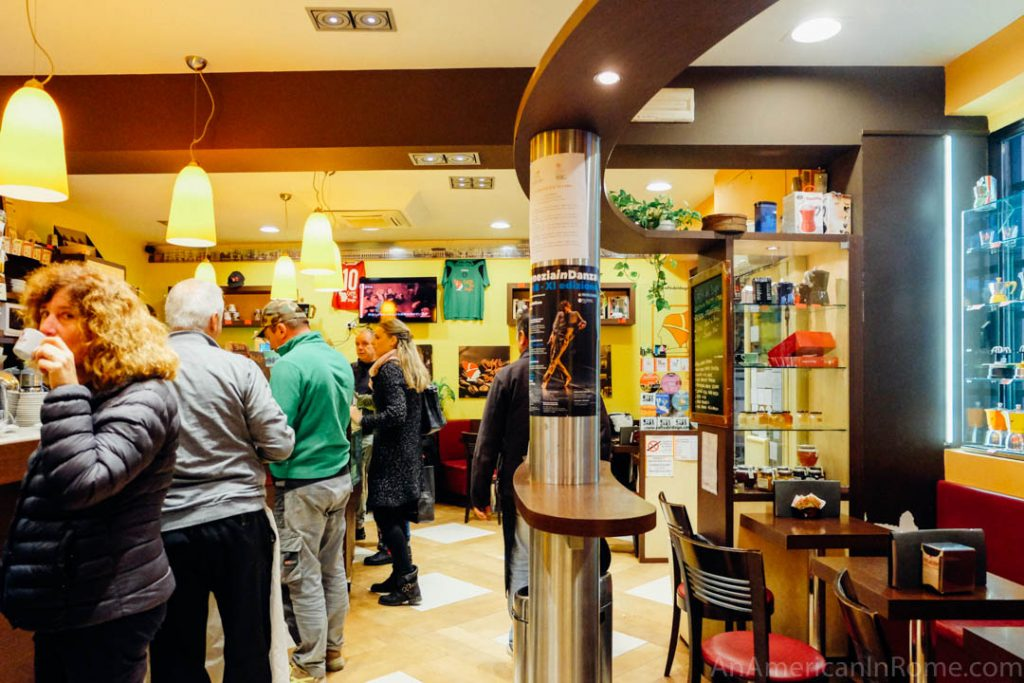 People inside Caffe del Doge in Venice Italy with the coffee bar the left and yellow walls with a few tables in back