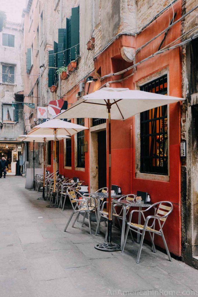 Outside of caffe del doge in Venice with orange walls and white umbrellas over outdoor tables