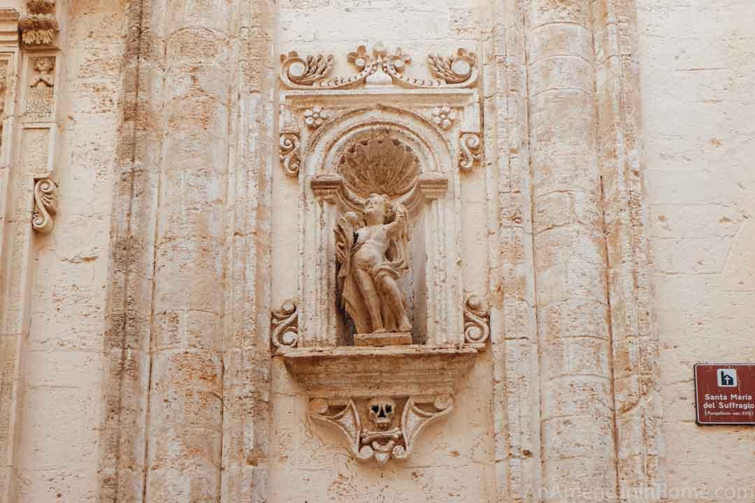 a stone angel decoration outside a catholic church in Puglia
