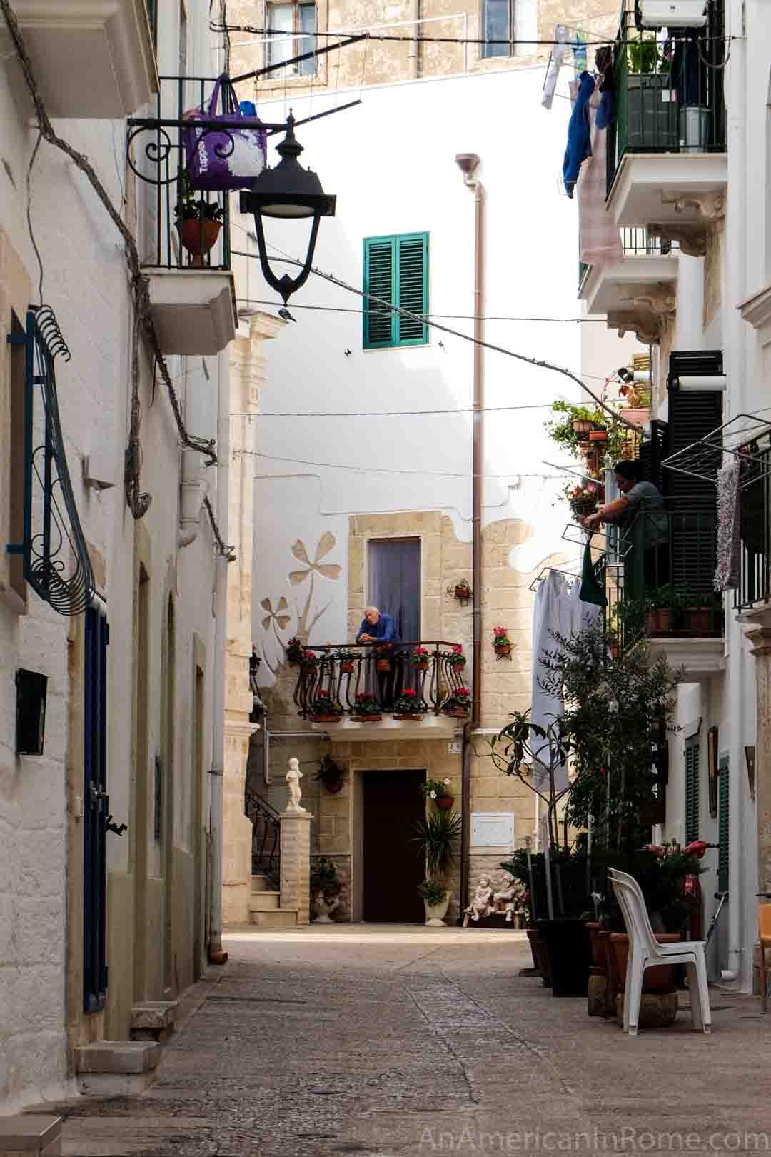 A man on his balcony in the white town of Polginano al Mare in Puglia