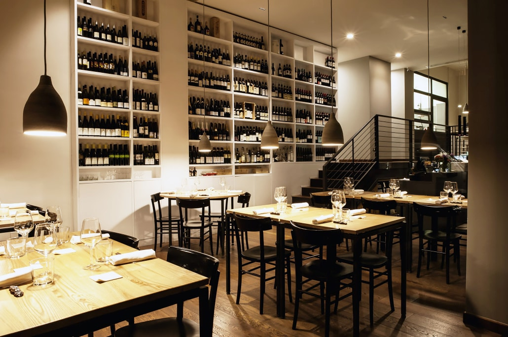 simple black chairs and walls of wine in the minimalist romantic restaurant Osteria Fernanda in rome