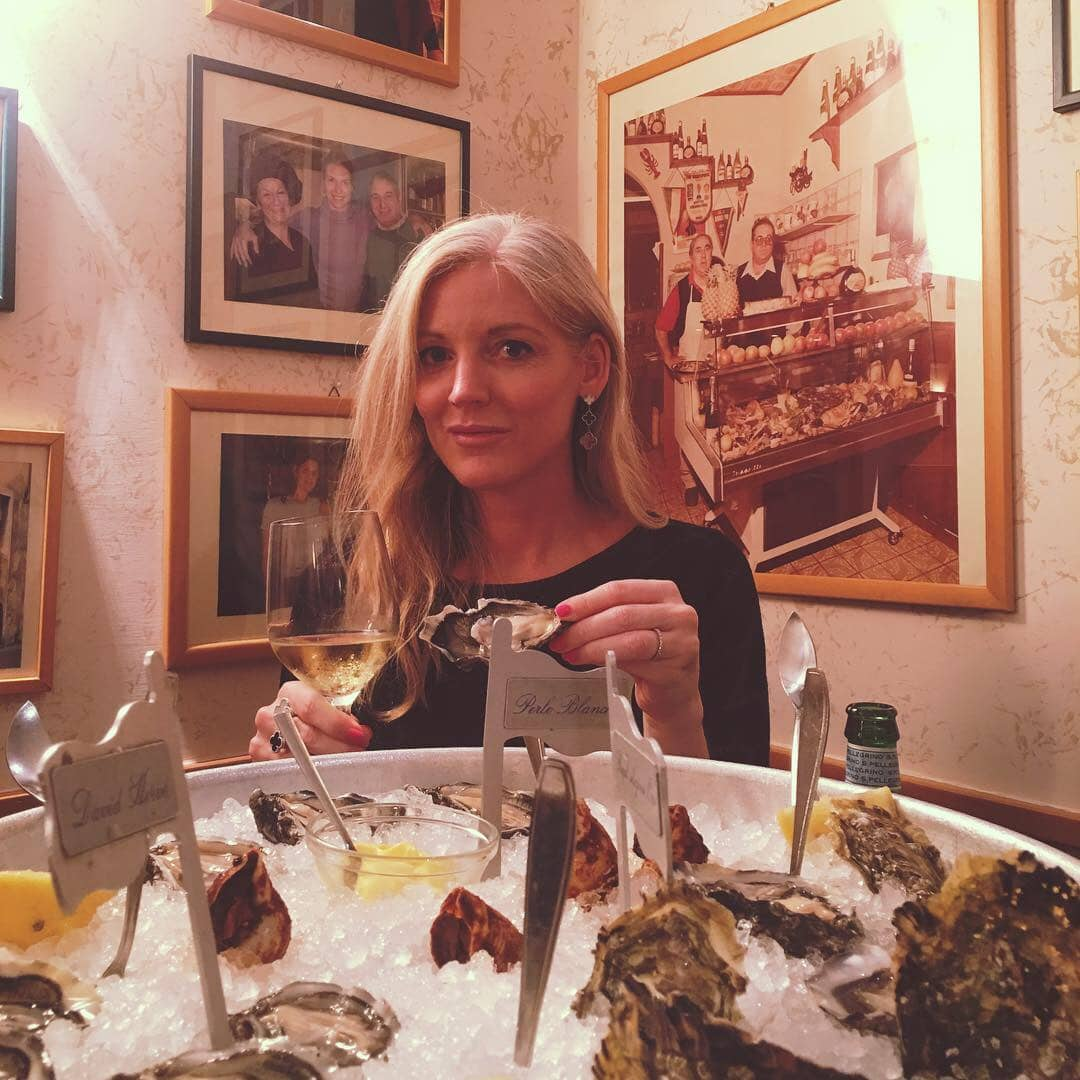 Joanne holding an oyster and a glass of wine at Da Benito e Gilberto with photographs on the wall behind