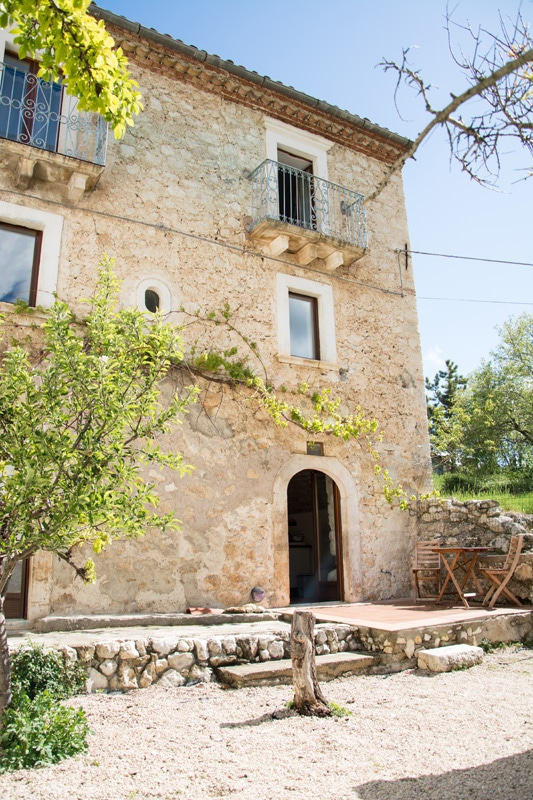 exterior of stone house you can win in Italy with green plants