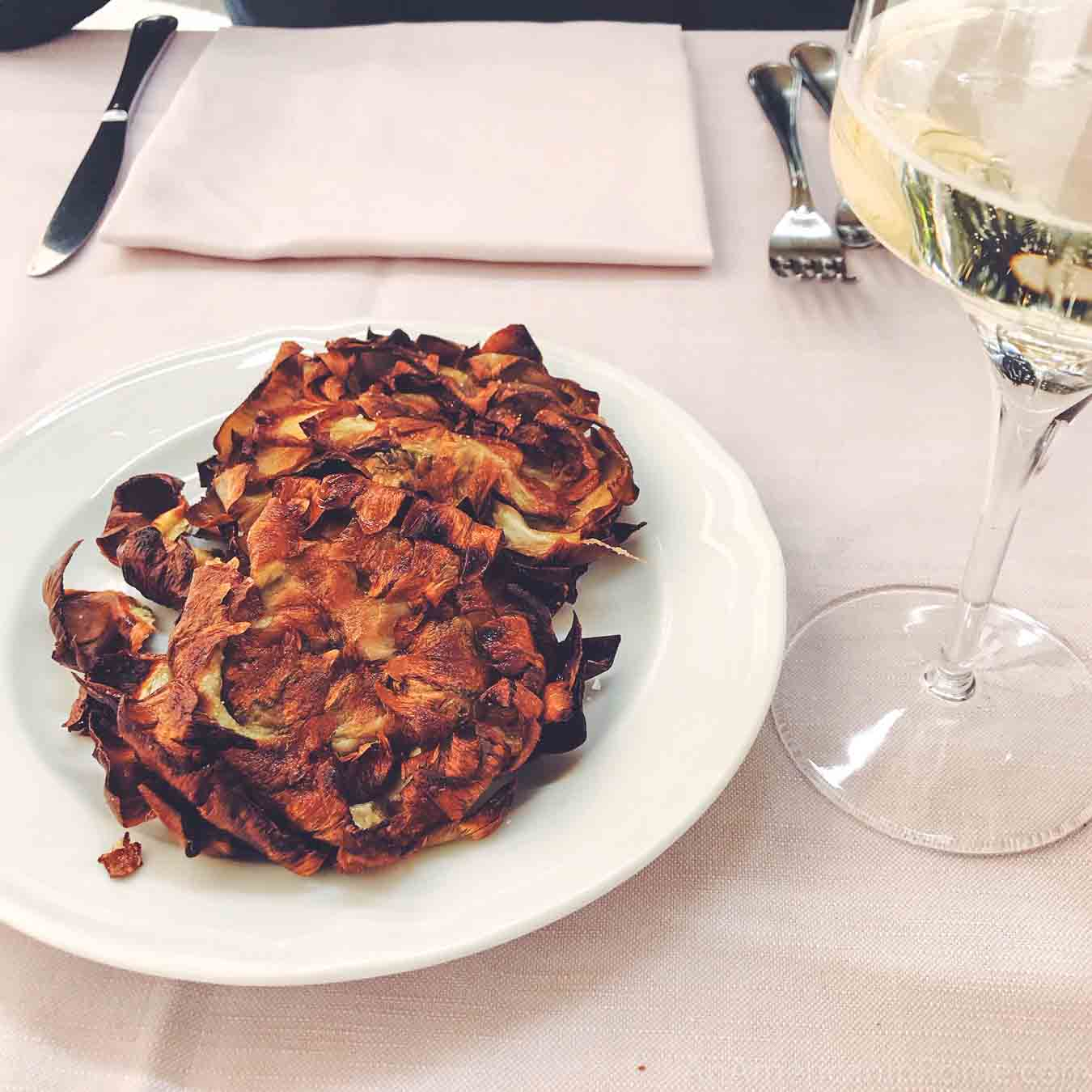 Two fried artichokes on a table with white wine