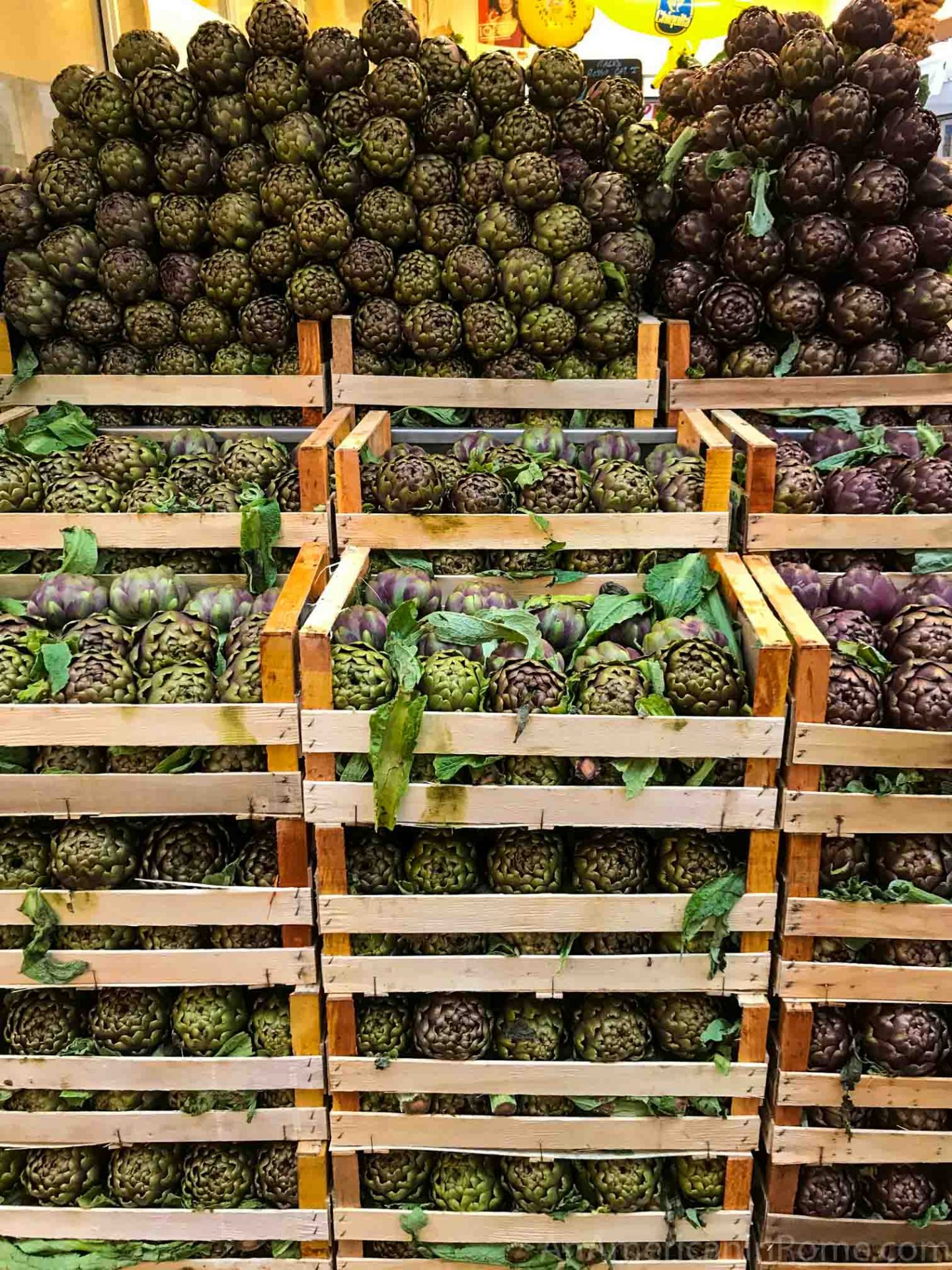 stacked crates and rows of artichokes in Rome