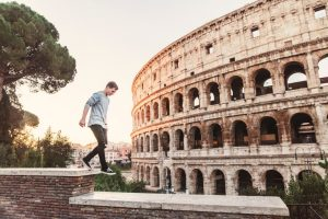 man walking on a wall with the colosseum close in the background