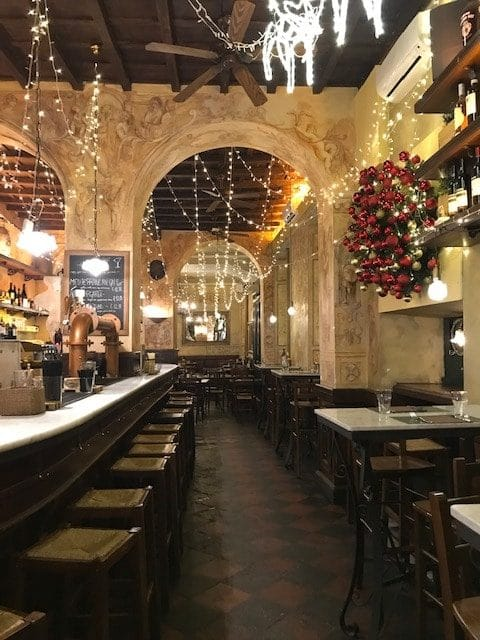 Rome restaurant with long dining room strung with lights and with dark wood stools at the bar