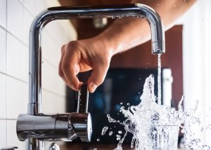 hand turning on sink for tap water