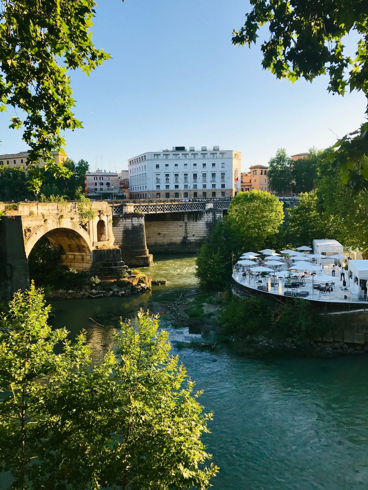 tables and white umbrellas set up along Rome river