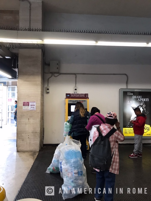 commuters in Rome recycling plastic bottles at metro station
