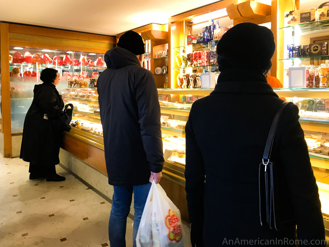 three people stand at counter in Pasticceria Tonolo