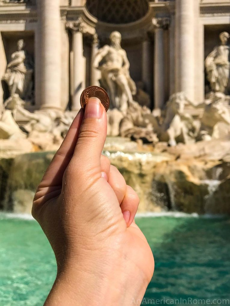hand throwing coin in Trevi fountain