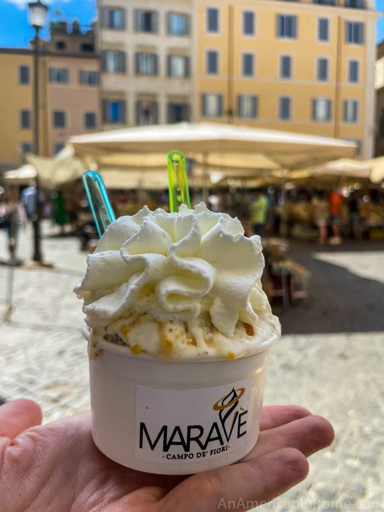 hand holding a cup of gelato with cream on top